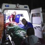 Medics load an injured person onto an ambulance, in Kerch, Crimea, Wednesday Oct. 17, 2018. Russian officials says an 18-year-old student attacked his vocational school in Crimea, going on a rampage that killed 17 students and left more than 40 people wounded before killing himself. (Viktor Korotaev/Kommersant Photo via AP)