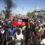 Demonstrators hold up a former Haitian flag with a picture of independence hero Jean Jacques Dessallines, during a protest demanding to know how Petro Caribe funds have been used by the current and past administrations, in Port-au-Prince, Haiti, Wednesday, Oct. 17, 2018. Much of the financial support to help Haiti rebuild after the 2010 earthquake comes from Venezuela's Petro Caribe fund, a 2005 pact that gives suppliers below-market financing for oil and is under the control of the central government. (AP Photo/Dieu Nalio Chery)