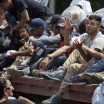 Migrantes hondureños que forman parte de una caravana que intenta llegar a Estados Unidos viajan gratis en el remolque de un camión, en Teculutan, Guatemala, el 17 de octubre de 2018. (AP Foto/Moisés Castillo)