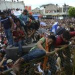 Thousands of Honduran migrants rush across the border towards Mexico, in Tecun Uman, Guatemala, Thursday, Oct. 18, 2018. Migrants broke down the gates at the border crossing and began streaming toward a bridge into Mexico. After arriving at the tall, yellow metal fence some clambered atop it and on U.S.-donated military jeeps. Young men began violently tugging on the barrier and finally succeeded in tearing it down. (AP Photo/Oliver de Roos)