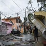 Residents of San Juan, Puerto Rico, deal with damages to their homes on September 20, 2017, as Hurricane Maria batters the island.  Maria slammed into Puerto Rico on Wednesday, cutting power on most of the US territory as terrified residents hunkered down in the face of the island's worst storm in living memory. After leaving a deadly trail of destruction on a string of smaller Caribbean islands, Maria made landfall on Puerto Rico's southeast coast around daybreak, packing winds of around 150mph (240kph).  / AFP / Hector RETAMAL
