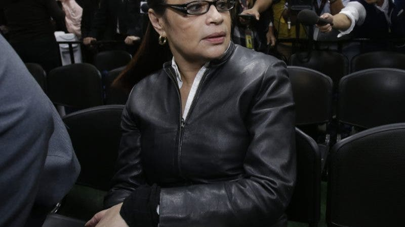 Guatemala's former Vice President Roxana Baldetti tries to evade journalists after she was sentenced to more than 15 years in prison for involvement in a fraudulent state contract to decontaminate a major lake, in Guatemala City, early Tuesday, Oct. 9, 2018. Baldetti has consistently denied wrongdoing. She resigned from the vice presidency in 2015 while facing corruption charges in a separate case. (AP Photo/Moises Castillo)