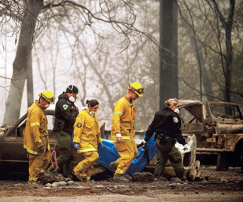 Firefighters recover the body of a Camp Fire victim at the Holly Hills Mobile Estates on Wednesday, Nov. 14, 2018, in Paradise, Calif. Thousands of homes were destroyed when flames hit Paradise, a former gold-mining camp popular with retirees, on Nov. 8, killing multiple people in California's deadliest wildfire. (AP Photo/Noah Berger)