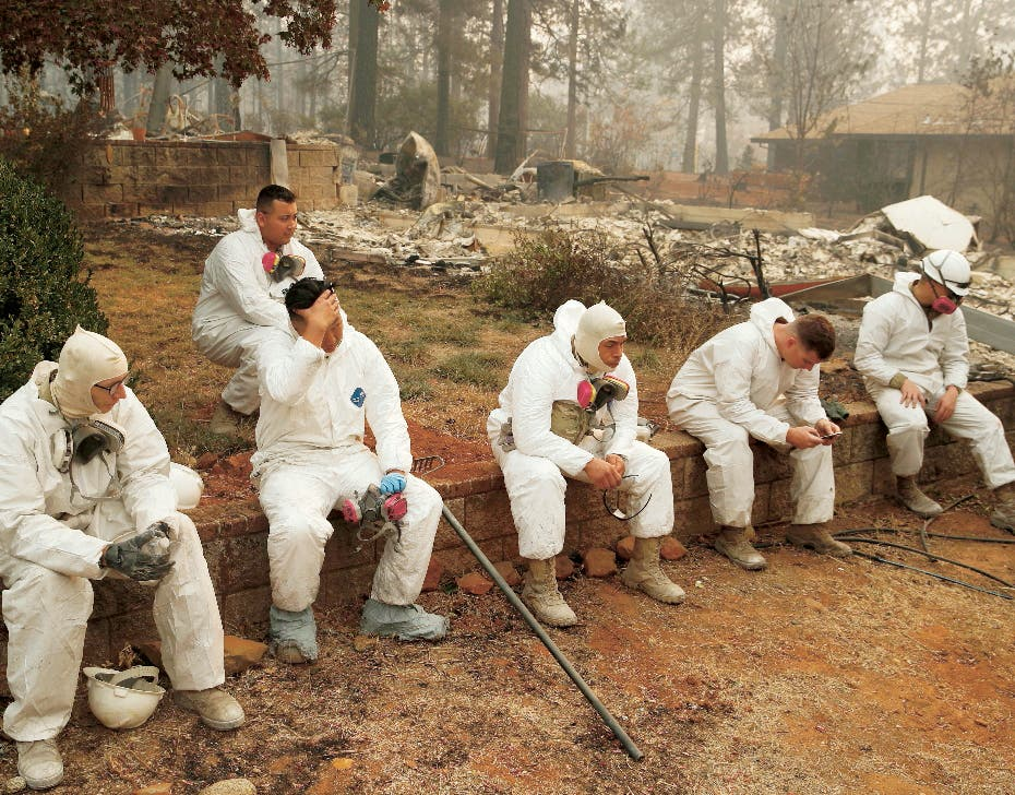 Members of the California Army National Guard take a break at they search burned homes for human remains at the Camp Fire, Thursday, Nov. 15, 2018, in Paradise, Calif. (AP Photo/John Locher)