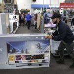 FILE - In this Nov. 23, 2017, file photo, Jesus Reyes pushes a television down an aisle as he shops at a Black Friday sale at a Best Buy store in Overland Park, Kan. A solid 70 percent of Americans plan to shop on Black Friday this year, according to a recent NerdWallet study conducted by The Harris Poll.  (AP Photo/Charlie Riedel, File)