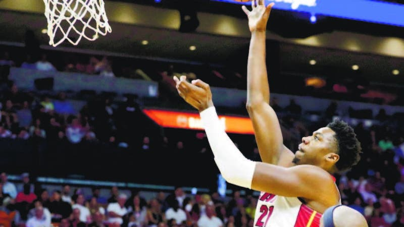 Miami Heat center Hassan Whiteside (21) shoots over San Antonio Spurs guard Derrick White (4) and forward Dante Cunningham (33) during the first half of an NBA basketball game, Wednesday, Nov. 7, 2018, in Miami. (AP Photo/Lynne Sladky)