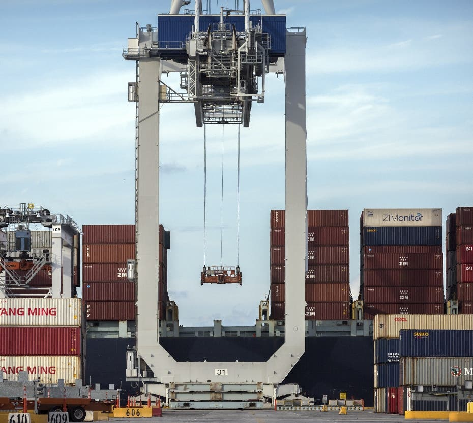 FILE - In this Thursday, July 5, 2018, photo, a ship to shore crane prepares to load a 40-foot shipping container onto a container ship at the Port of Savannah in Savannah, Ga. After galloping along for the past two years, the global economy is showing signs of weakening, with the United States, China and Europe all facing the rising threat of a slowdown. Few economists foresee an outright global recession within the next year. But the synchronized growth that powered most major economies since 2017 appears to be fading. (AP Photo/Stephen B. Morton, File)