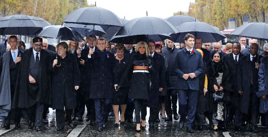 (From L) Morocco's Prince Moulay Hassan, Moroccan King Mohammed VI, German Chancellor Angela Merkel, French President Emmanuel Macron and his wife Brigitte Macron, Canadian Prime Minister Justin Trudeau, Niger's President's wife Lalla Malika Issoufou, Niger's President Mahamadou Issoufou and Republic of Guinea's President Alpha Conde walk towards the Arc de Triomphe, in Paris, France, as part of the commemorations marking the 100th anniversary of the 11 November 1918 armistice, ending World War I, Sunday, Nov. 11, 2018. (Ludovic Marin/Pool Photo via AP)