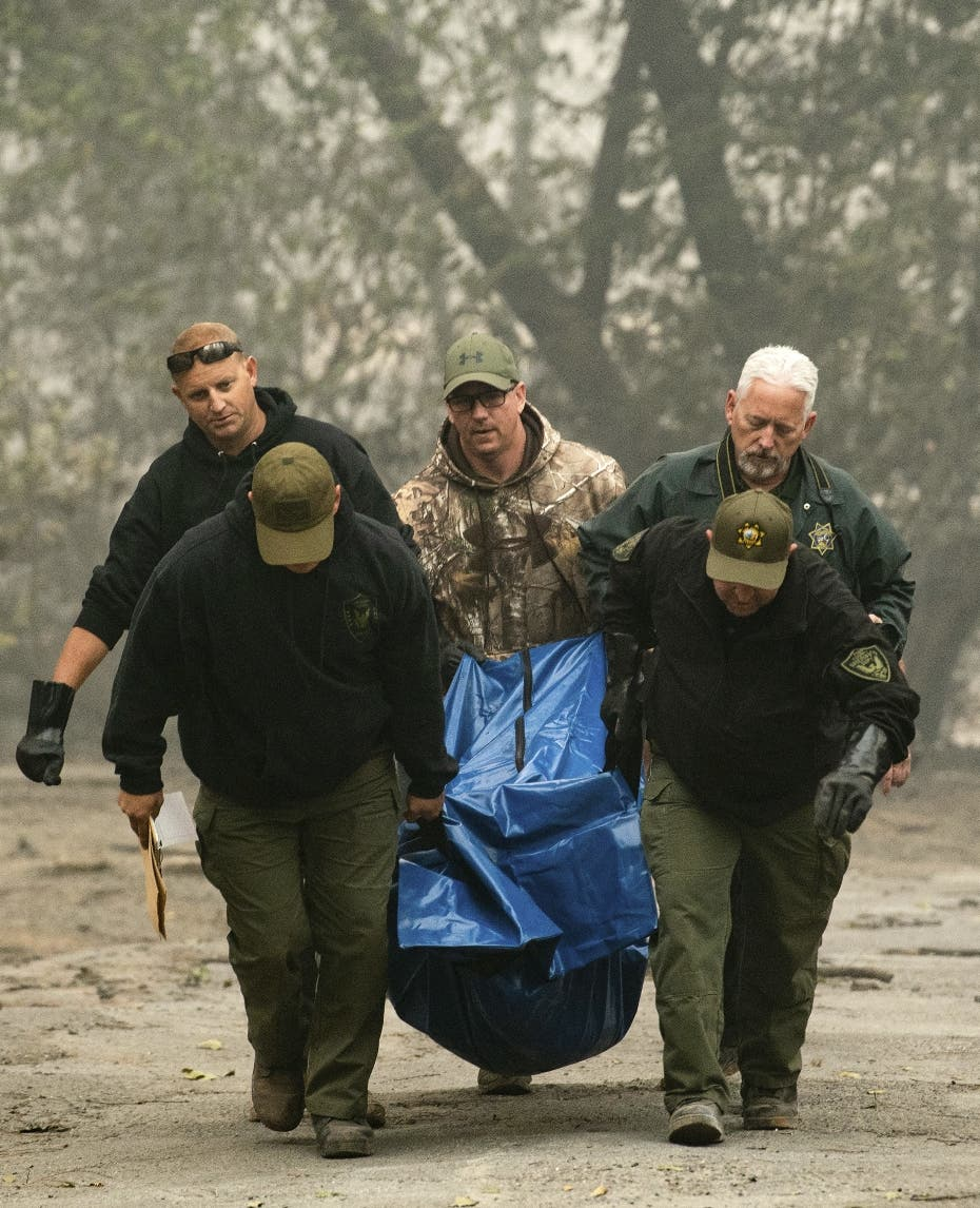 Sheriff's deputies recover the remains of a victim of the Camp Fire on Saturday, Nov. 10, 2018, in Paradise, Calif. (AP Photo/Noah Berger)