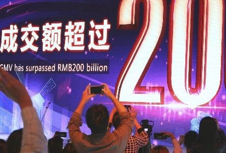 Journalists record  the moment after Alibaba's 11.11 Global Shopping Festival also known as Singles Day breaks the RMB200 billion or US$28.75 billion mark near the end of the 24 hours online shopping event in Shanghai, China, Sunday, Nov. 11, 2018. The spending binge has for years eclipsed Cyber Monday in the U.S. for online purchases made on a single day. This year's tally breaks from gloomy forecasts about the world's second-largest economy, which is struggling with a tariff war with the U.S., a stock market slump and slowing overall growth. (AP Photo/Ng Han Guan)
