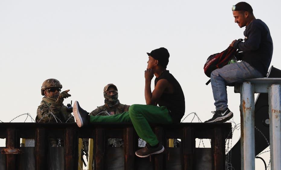 Agentes de una patrulla fronteriza de Estados Unidos (izquierda) hablan con dos migrantes centroamericanos sentados sobre la estructura que separa México de Estados Unidos, el 14 de noviembre de 2018, en Tijuana, México. (AP Foto/Gregory Bull)