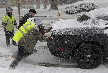 A police officer and others help push a car that was unable to gain traction on the snowy roads in Mt. Holly, N.J., Thursday, Nov. 15, 2018.  A mix of rain, sleet and snow started falling late Thursday morning in southern areas and was expected to soon move across the state.  (AP Photo/Seth Wenig)