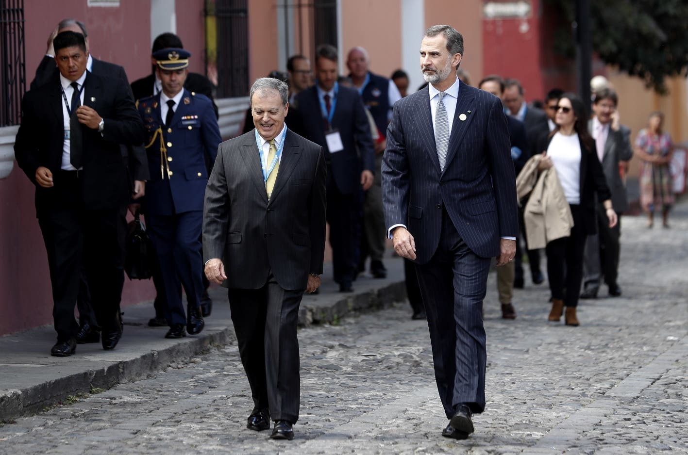 Spain's King Felipe, front right, is accompanied by Spain's ambassador to Guatemala, Alfonso Portabales, as they walk through the streets of Antigua, Guatemala, Thursday, Nov. 15, 2018. The King is taking part in the XXVI Iberoamerican Summit, a biennial two-day meeting of heads of state from Latin America and the Iberian Peninsula. (AP Photo/Moises Castillo)
