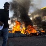 A youth runs past a burning roadblock during a strike that is part of protests demanding to know how Petro Caribe funds have been used by the current and past administrations, in Port-au-Prince, Haiti, Monday, Nov. 19, 2018. Much of the financial support to help Haiti rebuild after the 2010 earthquake comes from Venezuela's Petro Caribe fund, a 2005 pact that gives suppliers below-market financing for oil and is under the control of the central government. (AP Photo/Dieu Nalio Chery)