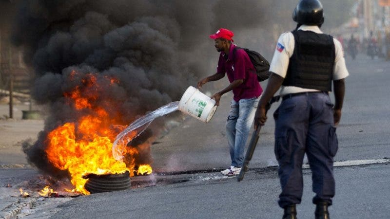 A national police officer watches as a resident attempts to put out burning tires during a countrywide protest over allegations of government corruption, in Port-au-Prince, Haiti, Tuesday, Nov. 20, 2018. At least eight deaths have been reported in clashes between protesters and police since the protests began on Sunday. (AP Photo/Dieu Nalio Chery)