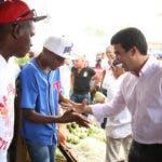 Wellington Arnaud saludando a trabajadores del mercado de Higüey