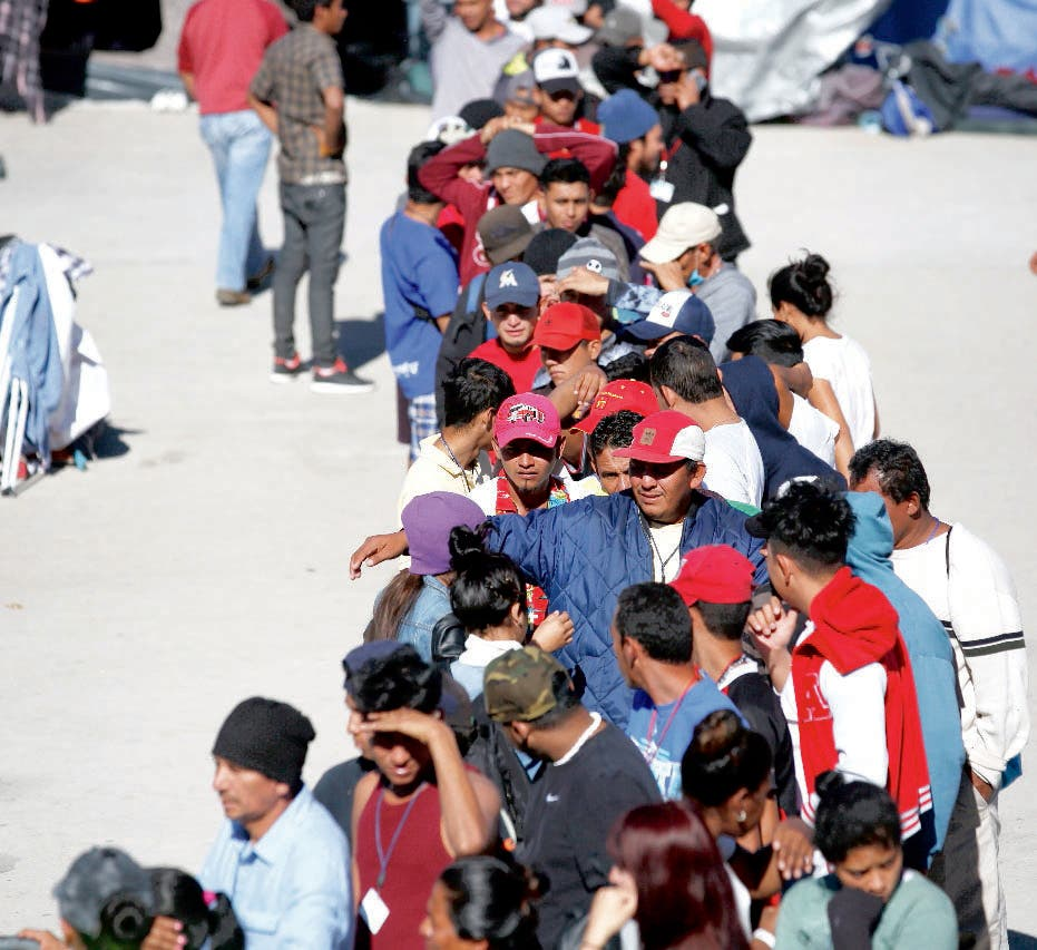 Migrants stand in line to pick out donated clothing, at the Barretal shelter for Central Americans who arrived in caravans over the past two months and hope to enter the U.S., in Tijuana, Mexico, Thursday, Dec. 13, 2018. (AP Photo/Moises Castillo)