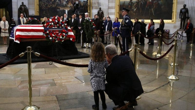 Rep. Patrick McHenry, R-N.C., kneels alongside his daughter Cecelia near the flag-draped casket of former President George H.W. Bush as he lies in state in the Capitol Rotunda in Washington, Tuesday, Dec. 4, 2018. (AP Photo/Patrick Semansky)