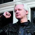 (FILES) This file photo taken on May 19, 2017 shows Wikileaks founder Julian Assange raising his fist prior to addressing the media on the balcony of the Embassy of Ecuador in London on May 19, 2017. Britain said on January 11, 2018 it has denied a request by Ecuador to issue diplomatic status to WikiLeaks founder Julian Assange, who has been living in the country's London embassy since 2012. / AFP / Justin TALLIS