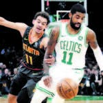 Boston Celtics guard Kyrie Irving, right, drives past Atlanta Hawks guard Trae Young, left, in the first quarter of an NBA basketball game, Friday, Dec. 14, 2018, in Boston. (AP Photo/Elise Amendola)