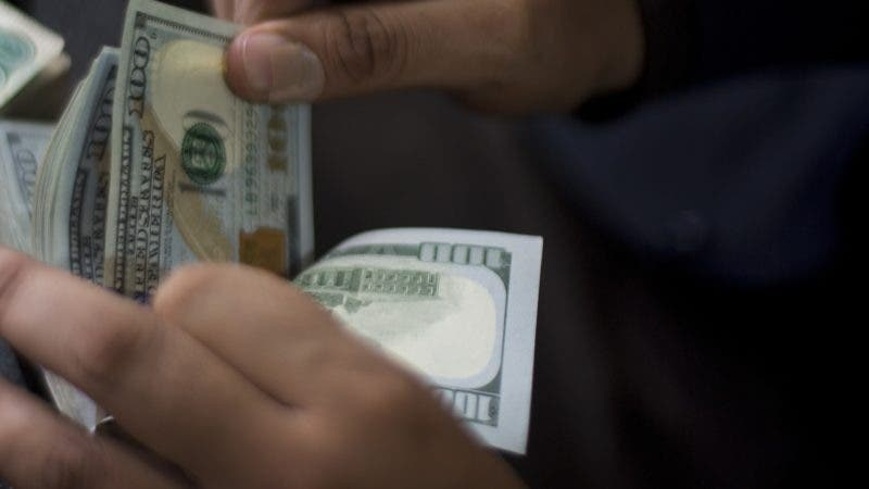A Pakistani money changer counts US dollar bills in Islamabad, Pakistan, Friday, Nov. 30, 2018. Pakistan's currency has plunged further as the country is mired in a financial crisis and seeking an $8 billion bailout package from the International Monetary Fund. The Pakistani rupee was trading at 142 to the dollar on Friday, a decline from 133.90 rupees to $1 at close of business the previous day. (AP Photo/B.K. Bangash)