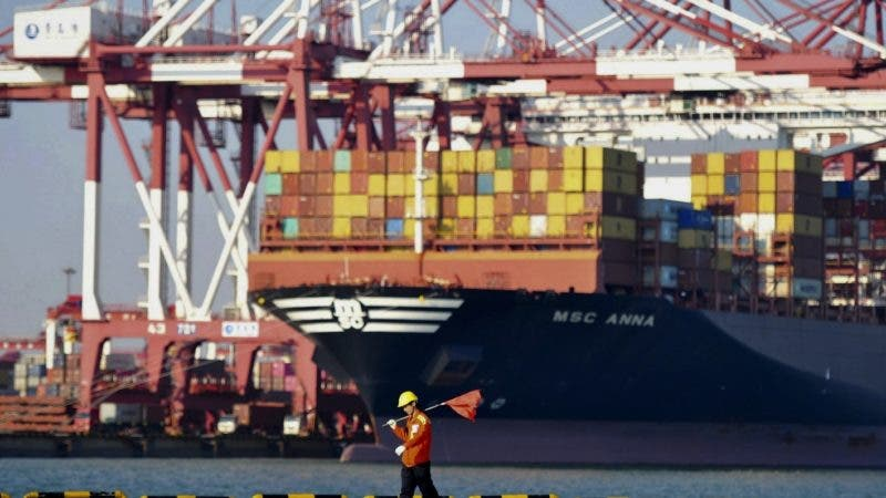 FILE - In this Oct. 12, 2018, file photo, a worker walks by a container ship docked at a port in Qingdao in east China's Shandong province. China's factory activity weakened in November, an industry group reported Friday, Nov. 30, 2018, adding to pressure on Beijing ahead of talks between Presidents Donald Trump and Xi Jinping over an escalating tariff battle. (Chinatopix via AP, File)