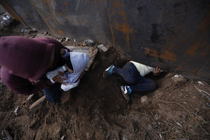 Migrantes cruzan muro fronterizo por arriba o por debajo