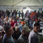 In this Nov. 27, 2018 photo, migrants who traveled in a caravan stand in line at a job fair in Tijuana, Mexico. Mexican authorities have encouraged all of the migrants to regularize their status in Mexico and seek work. (AP Photo/Ramon Espinosa)