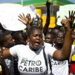 "A woman wears a t-shirt with text written in Creole that reads ""Where are the PetroCaribe Funds?"" while chanting anti-government slogan during a protest in front of the Superior Court of Accounts and Administrative Litigation, to demand an accounting of the Petrocaribe funds, in Port-au-Prince, Haiti, Friday, Aug. 24, 2018. Venezuela is one of the biggest donors to help impoverished Haiti rebuild from the catastrophic 2010 earthquake. Much of that support comes from Venezuela's PetroCaribe fund, a pact created in 2005 that gives suppliers below-market financing for oil. ( AP Photo/Dieu Nalio Chery)"