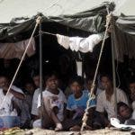 Rohingya refugees sit in their encampment at a military base Friday, Jan. 30, 2009  on Sabang, off the Coast of Banda Aceh, Indonesia.  The Indonesian government is decding what to do with the 193 Rohingyas who were rescued from a decrepit boat found drifting with inadequate supplies by Acehnese fishermen. (AP Photo/Binsar Bakkara)