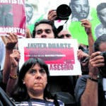 "Journalists and activists hold up cut-out images of slain photojournalist Ruben Espinosa during a protest at MexicoCity's Angel of the Independence monument, Sunday, Aug. 2, 2015. Mexico City officials said Sunday they are pursuing all lines of investigation into the killing Espinosa and four other women whose bodies were found in the capital, where he had fled from the state of Veracruz because of harassment. According to the Committee to Protect Journalists, 11 journalists have been killed there since 2010, all during the administration of Gov. Javier Duarte. The signs held by the protesters read in Spanish ""Duarte Government, Murderer of Journalists"" and ""Javier Duarte, Assassin State.""  (AP Photo/Dario Lopez-Mills)"
