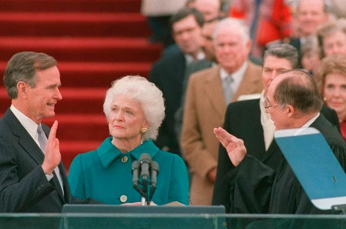 7. 20 de enero de 1989, el presidente George H.W. Bush levanta la mano derecha mientras toma posesión del cargo como presidente número 41 de los Estados Unidos por el presidente del Tribunal Supremo William Rehnquist, en el frente occidental del Capitolio, cuando la primera dama Barbara Bush sostiene la biblia de su esposo.