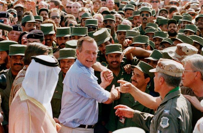 11. 22 de noviembre de 1990, el presidente George H.W. Bush es recibido por las tropas sauditas y otras personas cuando llega a Dhahran, Arabia Saudita, para una visita de Acción de Gracias.