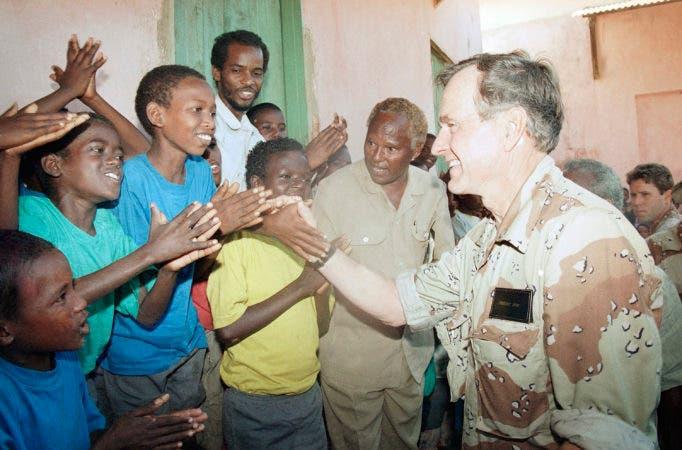 """13. 1 de enero de 1993, foto de archivo, el presidente de los Estados Unidos, George H.W. Bush saluda a los niños somalíes que lo aplauden durante una visita de dos días a un orfanato en Baidoa, Somalia, asolada por la hambruna, en una visita de dos días para revisar la Operación Restaurar la Esperanza. En los últimos días de su presidencia, George H.W. Bush comprometió a los militares estadounidenses a una misión que muchos lamentarían más tarde, ordenando a más de 20,000 soldados a Somalia """"salvar a miles de inocentes de la muerte""""."""