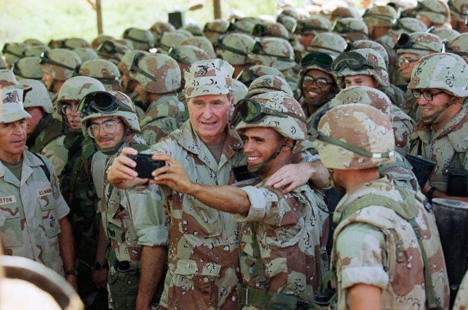 """12. 1 de enero de 1993, el Presidente de los EE. UU., George H.W. Bush sostiene una cámara al alcance de la mano para tomarse una selfie con los marines en el aeropuerto de Baidoa en Baidoa, Somalia. Bush envió tropas de EE. UU. Para ayudar a los somalíes hambrientos durante su presidencia y luego se unió a su único rival político, Bill Clinton, para recaudar fondos para las víctimas de desastres naturales. Todo fue parte de la visión de Bush de lo que llamó """"una nación más amable y gentil"""". Bush fue un humanitario y convirtió el voluntariado en un sello distintivo de su presidencia desde 1989 hasta 1993."""
