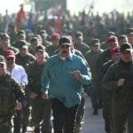 In this photo released to the media by Miraflores presidential palace press office, Venezuelan President Nicolas Maduro, center, jogs alongside his Defense Minister Vladimir Padrino Lopez, right, and soldiers as he visits Ft. Paramacay in Carabobo state, Venezuela, Sunday, Jan. 27, 2019. Opposition lawmaker Juan Guaido has declared himself Venezuela's legitimate leader, as embattled socialist Maduro holds the reins of power. (Marcelo Garcia/Miraflores presidential palace press office via AP)