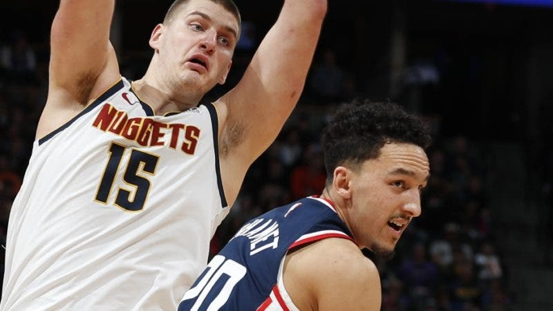 Denver Nuggets center Nikola Jokic, (15)  throws a pass over Los Angeles Clippers guard Landry Shamet in the second half of an NBA basketball game Sunday, Feb. 24, 2019, in Denver. The Nuggets won 123-96. (AP Photo/David Zalubowski)
