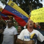 "Venezuelans living in Colombia sing their national anthem as they protest the government of Venezuela's President Nicolas Maduro in Cucuta, Colombia, Tuesday, Feb. 12, 2019, on the border with Venezuela. Venezuela's opposition called its supporters into the streets in a campaign to break the military's support of Maduro, who refuses to let emergency food and medicine from the U.S. across the border. The sign reads in Spanish: ""Juan Guaido, here are your people,"" referring to the opposition leader who declared himself interim president. (AP Photo/Fernando Vergara)"