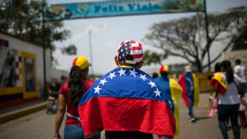 Larry Rios, bearing a Venezuelan national flag on his shoulders and sporting a stars-and-stripes cap, makes his way to the Venezuela Aid Live concert, near the Simon Bolivar International Bridge, in San Antonio del Tachira, Venezuela, Friday, Feb. 22, 2019, on the border with Colombia. Venezuela's power struggle is set to convert into a battle of the bands Friday when musicians demanding Nicolas Maduro allow in humanitarian aid and those supporting the embattled leader's refusal sing in rival concerts being held at both sides of a border bridge where tons of donated food and medicine are being stored. (AP Photo/Rodrigo Abd)