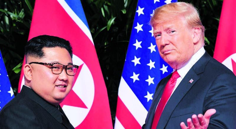 US President Donald Trump (R) gestures as he meets with North Korea's leader Kim Jong Un (L) at the start of their historic US-North Korea summit, at the Capella Hotel on Sentosa island in Singapore on June 12, 2018. Donald Trump and Kim Jong Un have become on June 12 the first sitting US and North Korean leaders to meet, shake hands and negotiate to end a decades-old nuclear stand-off. / AFP / SAUL LOEB