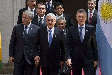 Colombia's President Ivan Duque, front row, from left, Chile's President Sebastian Pinera, Argentina's President Mauricio Macri; second row, from left, Brazil's President Jair Bolsonaro, Ecuador's President Lenin Moreno; last row, from left, Peru's President Martin Vizcarra, Guyana's Ambassador George Talbot and Paraguay's President Mario Abdo Benitez, arrive for a signing ceremony at the Prosur Summit outside the presidential palace La Moneda, in Santiago, Chile, Friday, March 22, 2019. (AP Photo/Esteban Felix)