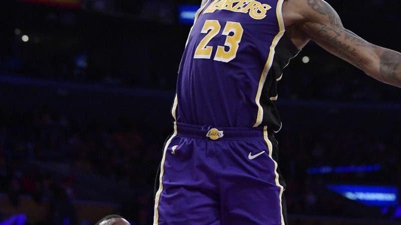 Los Angeles Lakers forward LeBron James goes up for a dunk as Denver Nuggets forward Paul Millsap watches during the second half of an NBA basketball game Wednesday, March 6, 2019, in Los Angeles. The Nuggets won 115-99. (AP Photo/Mark J. Terrill)