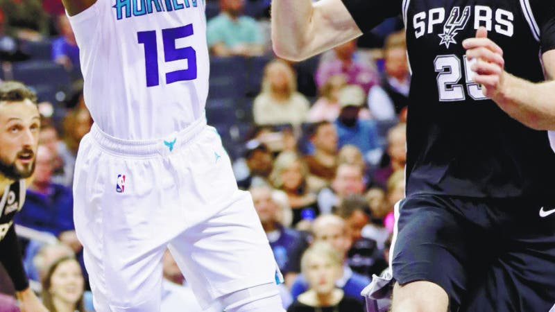 Charlotte Hornets' Kemba Walker (15) drives past San Antonio Spurs' Jakob Poeltl (25) during the first half of an NBA basketball game in Charlotte, N.C., Tuesday, March 26, 2019. (AP Photo/Chuck Burton)