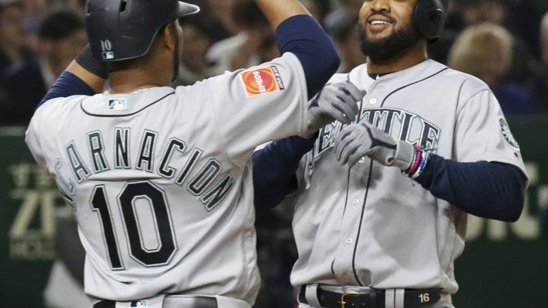 Seattle Mariners' Domingo Santana, right, celebrates with teammate Edwin Encarnacion after hitting a grand slam off Oakland Athletics starter Mike Fiers in the third inning of Game 1 of their Major League opening series baseball game at Tokyo Dome in Tokyo, Wednesday, March 20, 2019.  (AP Photo/Koji Sasahara)