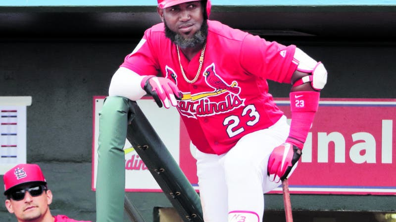 St. Louis Cardinals' Harrison Bader, left, and St. Louis Cardinals' Marcell Ozuna, right, look out at the field from the dugout during an exhibition spring training baseball game Monday, March 18, 2019, in Jupiter, Fla. (AP Photo/Brynn Anderson)
