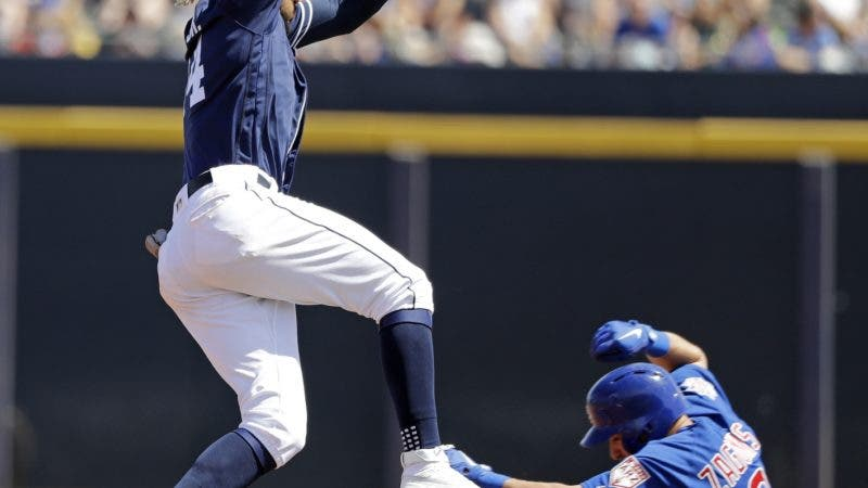 San Diego Padres shortstop Fernando Tatis Jr., left, leaps out of the way as Chicago Cubs' Mark Zagunis slides safely into second base with a stolen base during the fourth inning of a spring training baseball game Sunday, March 24, 2019, in Peoria, Ariz. (AP Photo/Elaine Thompson)
