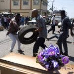 Protesters prepare to set tires alight next to the coffins containing the bodies of demonstrators who were killed during previous protests in Port-au-Prince, Haiti, Monday, March 4, 2019. Protesters are angry about skyrocketing inflation and the government's failure to prosecute embezzlement from a multi-billion Venezuelan program that sent discounted oil to Haiti. (AP Photo/Dieu Nalio Chery)
