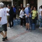 People buy bottled water during an electric blackout that renders apartment building water pumps inoperable in Caracas, Venezuela, Sunday, March 10, 2019. Power and communications outages continue to hit Venezuela, intensifying the hardship of a country paralyzed by economic and political crisis and heightening tension between the bitterly divided factions which accuse each other of being responsible for the collapse of the power grid. (AP Photo/Eduardo Verdugo)