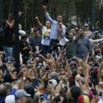 National Assembly President Juan Guaido, who declared himself interim president of Venezuela, speaks to supporters as he visits different anti-government protests in Caracas, Venezuela, Tuesday, March 12, 2019. At left of him is Liliana Lopez, wife of jailed politician Leopoldo Lopez. Guaido has declared himself interim president and demands new elections, arguing that President Nicolas Maduro's re-election last year was invalid. (AP Photo/Ariana Cubillos)