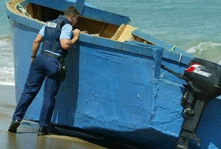 A Puerto Rican policeman takes a look inside the wooden boat where Dominican migrants came ashore in Dorado, Puerto Rico, Friday, Feb. 27, 2004. Migrants from the Dominican Republic were detained after the police searched them upon their arrival to U.S. territory in two wooden boats. (AP Photo/Ricky Arduengo).Yola de ilegales